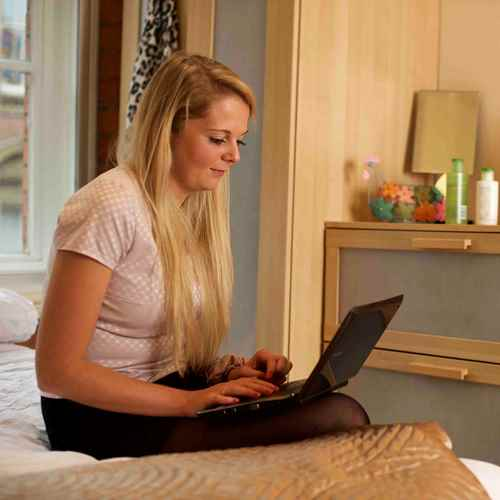 Woman sits on the side of her bed, looking at her laptop