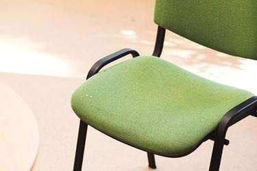 Green office chair on light brown floor