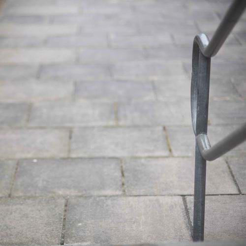 Grey paving slabs viewed from steps, a metal handrail to the right
