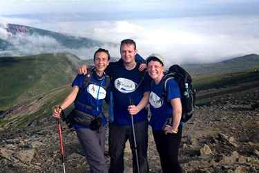 Group of three hikers in the peaks looking happy