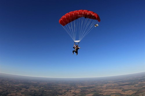 Skydiver mid-air with an open parachute