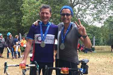 Two happy cyclists at the end of race with medals