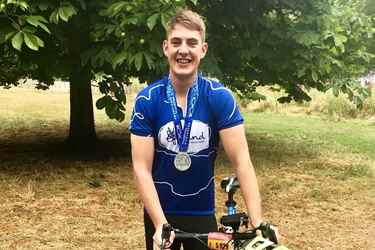 Happy cyclist in Mind top with medal
