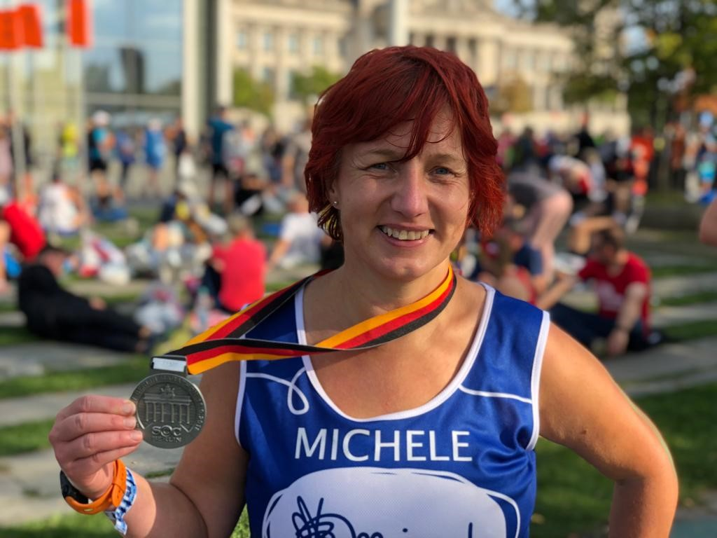 Berlin marathon lady with finishing medal looking happy