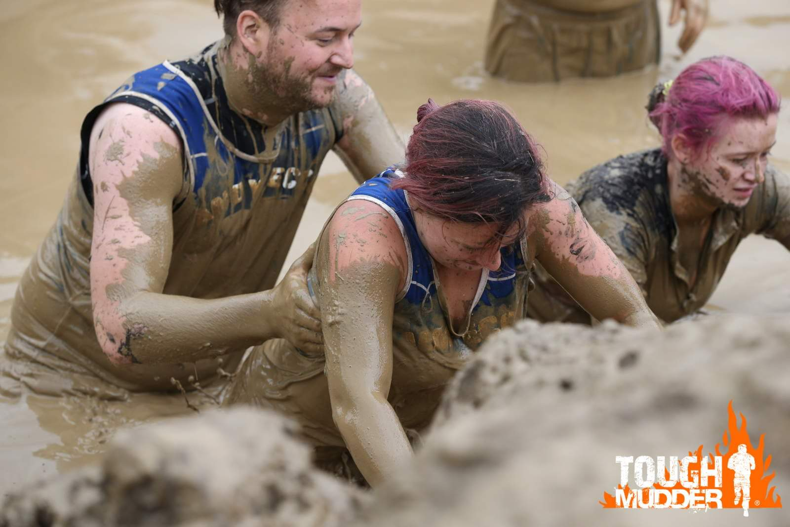 Group pushing through the mud at the Tough Mudder event