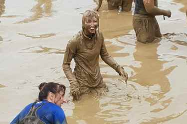 Person covered in mud looking very happy during Tough Mudder