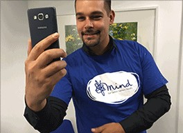 Jay wears a Mind t-shirt and is taking a selfie with his smartphone