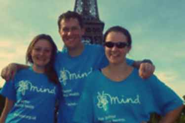 Mark in front of the Eiffel Tower wearing a Mind t-shirt with his arms around two others wearing the same top