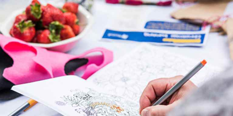 Someone is colouring in a mindful colouring book at their Crafternoon. There are some mouth watering strawberries to side - as a tasty snack