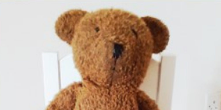 Small brown teddy bear in a white chair facing forwards