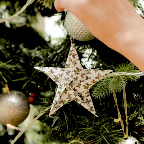 Origami star decoration being hung on tree