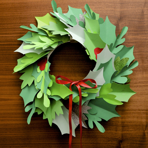 Paper Christmas wreath with red ribbon hung on door