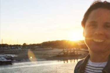 A woman looking at the camera with the sun setting behind her, with the sea, beach and docked boats.