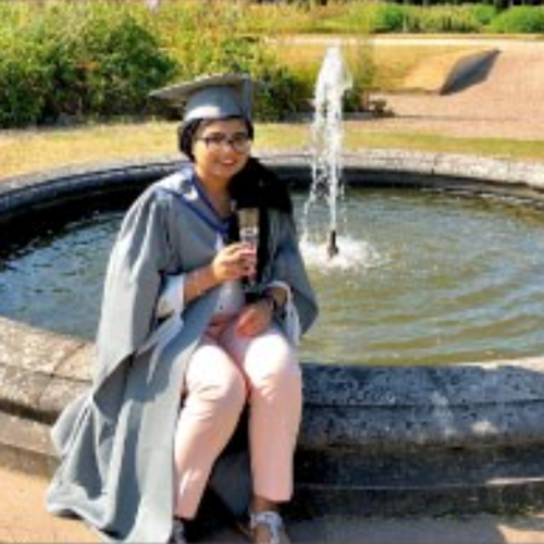 female wearing graduation robes and hat smiling sitting on the short wall of a water feature
