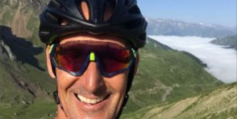 male wearing cycling helmet and sunglasses with a mountain terrain behind