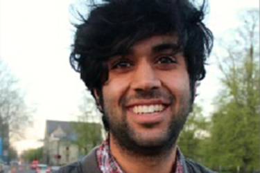 male with very black, thick hair smiling