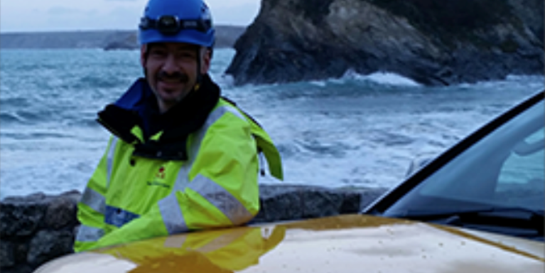 Male in high vis jacket standing by a car, with the sea behind him
