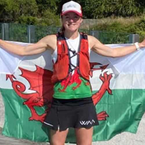 Menna in her running gear holding up a flag of Wales