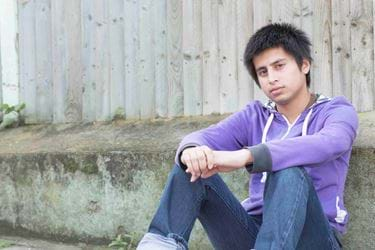 A young man in a purple hoodie and jeans with a neutral expression, sitting outside on the ground leaning against a fence.