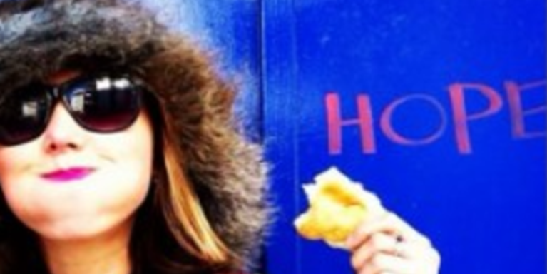 "photo of woman wearing a fluffy hat and sunglasses, smiling and holding a bread roll, in front of a blue wall with the word ""hope"" on it"