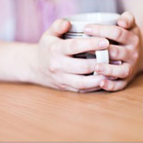 Hands holding a mug sitting on a desk