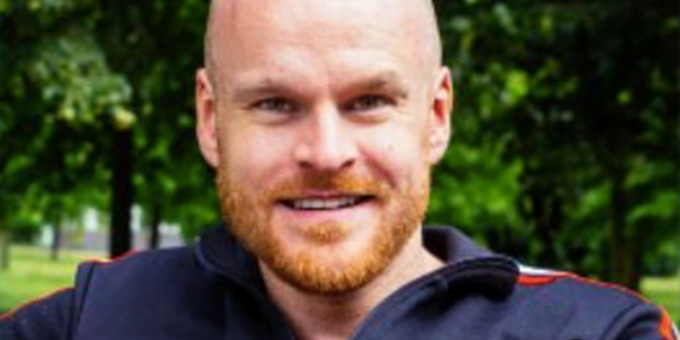 male with bald head and ginger beard smiling