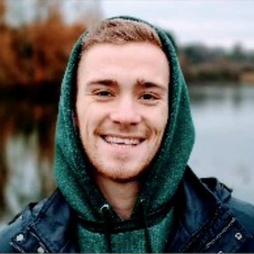 Male smiling with green hoodie on, with a lake behind him