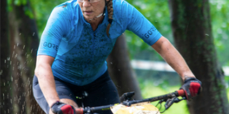 female muddy and on a bicycle