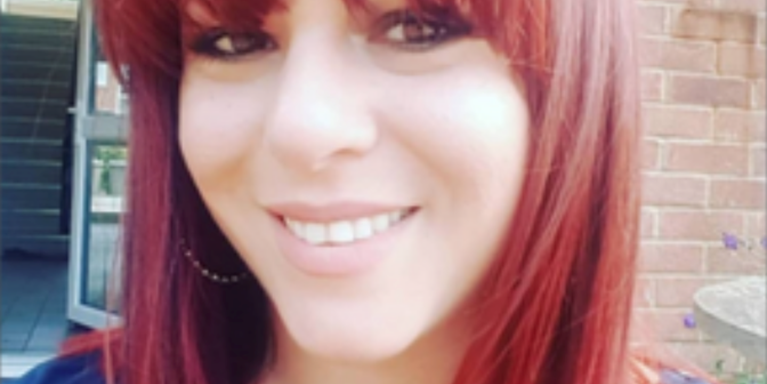 female smiling, with a full fringe and red hair