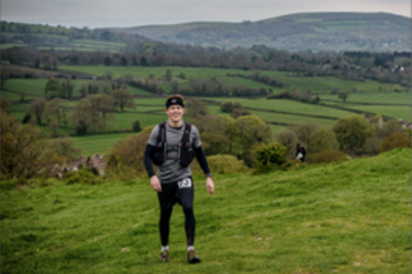 male in walking gear on a landscape with fields and hills