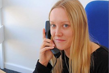 female smiling holding a landline phone to her ear